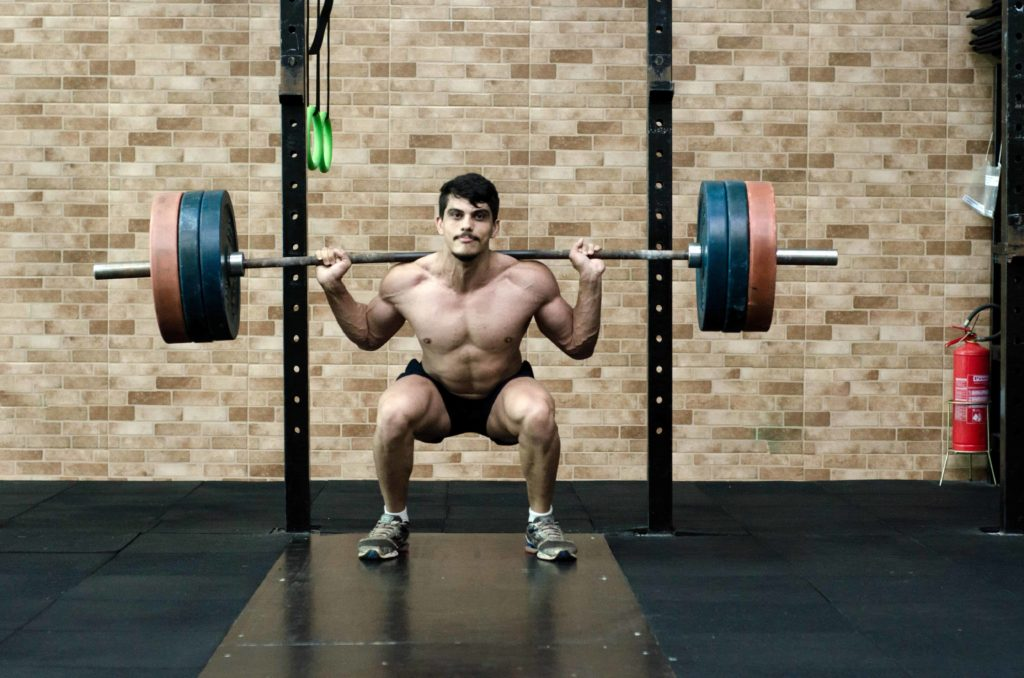 Weightlifter using compound lifts (squats) to build muscle.